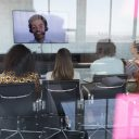 Business team attending video call with oversees colleague in a conference room at modern office