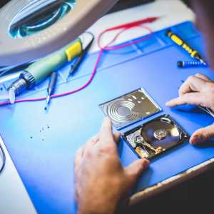 Worker fixing HDD disc in workshop.